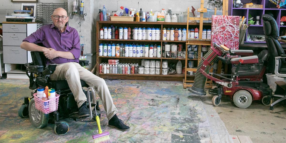 Portrait of Michael Bingham in colorful, paint-splattered art studio